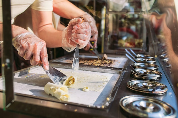 Roergebakken ijsrolletjes in de vriespan. organisch, natuurlijk gerold ijs, met de hand gemaakt dessert.