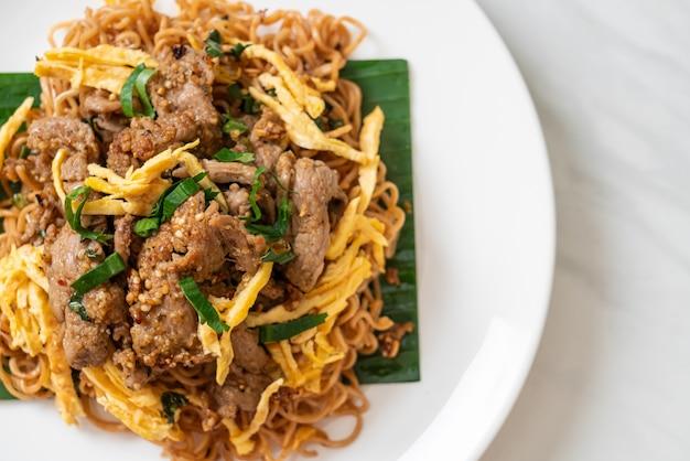 Roergebakken instantnoedel met varkensvlees en ei - aziatische lokale streetfoodstijl