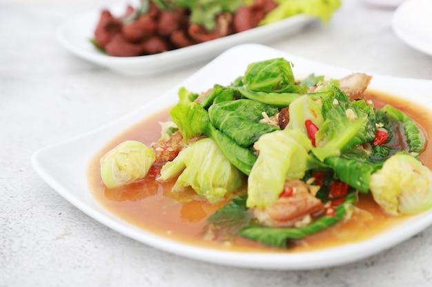 Roergebakken kool met knapperig varkensvlees in het favoriete menu van de witte schotel in het restaurant van thailand
