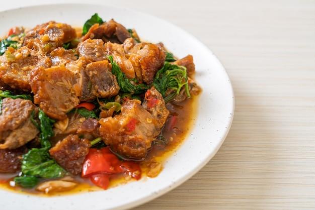 Roergebakken krokant buikspek en basilicum. aziatische lokale straatvoedselstijl