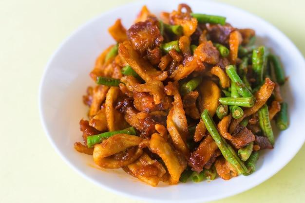 Roergebakken krokant varkensvlees en kousenband met thaise pittige currypasta op wit bord in thais eten