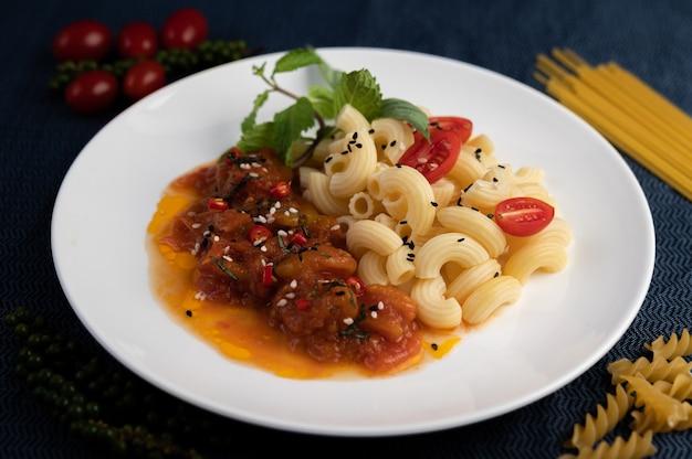 Roergebakken macaroni met tomaat, chili, peperzaadjes en basilicum in een witte schotel.