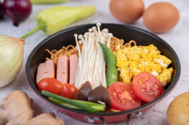 Roergebakken noedels die mais, champignons, tomaat, worst, edamame en lente-uitjes in een koekenpan combineren.