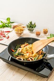 Roergebakken noedels met groente en vlees op de pan