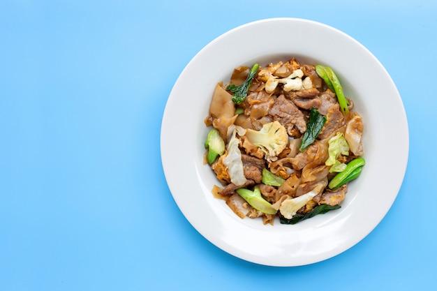 Roergebakken platte noedels en varkensvlees met sojasaus. bovenaanzicht