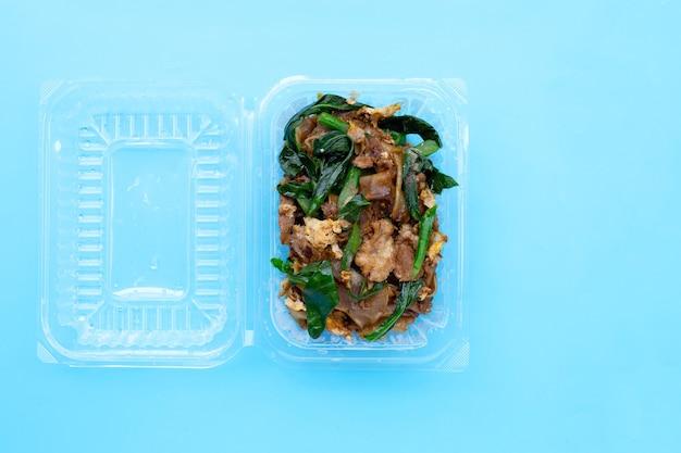 Roergebakken platte noedels en varkensvlees met sojasaus in plastic voedselcontainer. kopieer ruimte