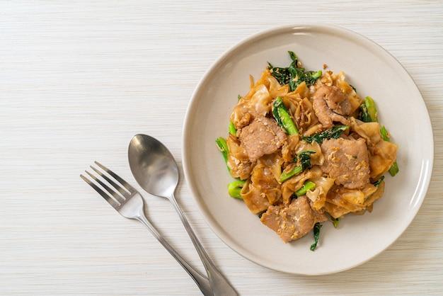 Roergebakken rijstnoedel met zwarte sojasaus en varkensvlees en boerenkool - aziatische eetstijl
