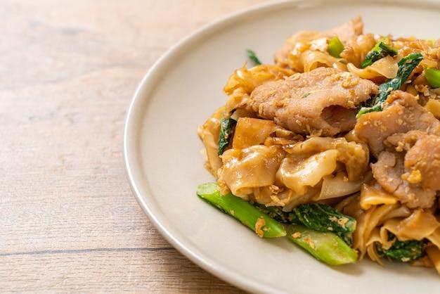 Roergebakken rijstnoedel met zwarte sojasaus en varkensvlees en boerenkool