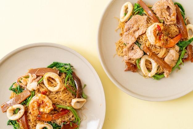 Roergebakken rijstvermicelli en watermimosa met gemengd vlees - aziatisch eten