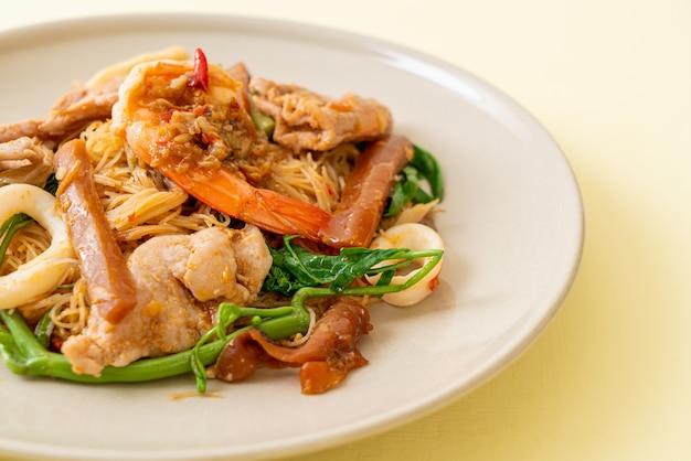 Roergebakken rijstvermicelli en watermimosa met gemengd vlees