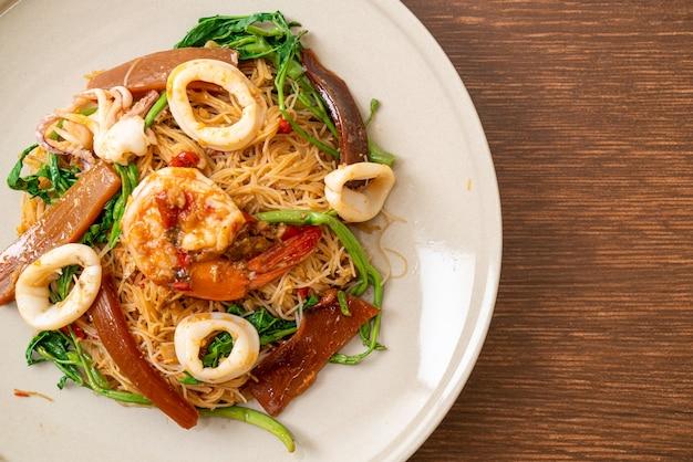Roergebakken rijstvermicelli en watermimosa met gemengde zeevruchten - asian food style
