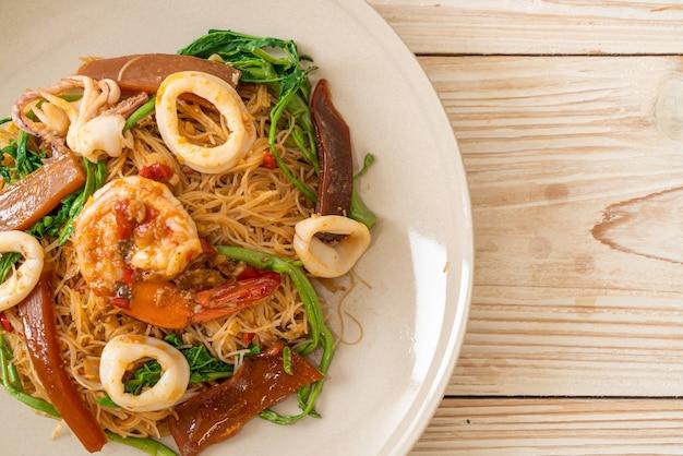 Roergebakken rijstvermicelli en watermimosa met gemengde zeevruchten - aziatische eetstijl