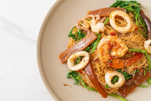 Roergebakken rijstvermicelli en watermimosa met gemengde zeevruchten - aziatische gerechten