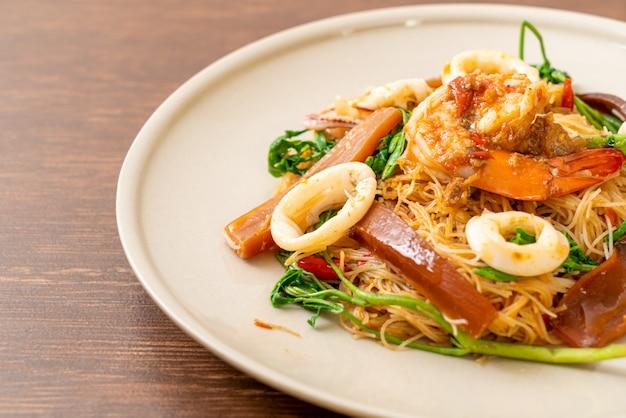 Roergebakken rijstvermicelli en watermimosa met gemengde zeevruchten