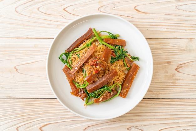 Roergebakken rijstvermicelli en watermimosa met ingelegde inktvis
