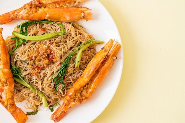 Roergebakken rijstvermicelli en watermimosa met riviergarnalen op plaat