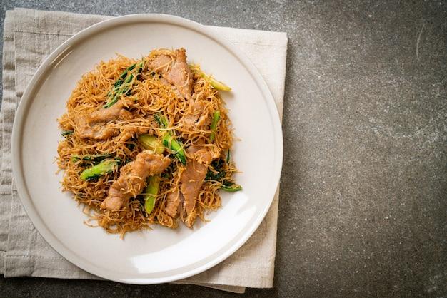 Roergebakken rijstvermicellinoedel met zwarte sojasaus en varkensvlees - aziatisch eten