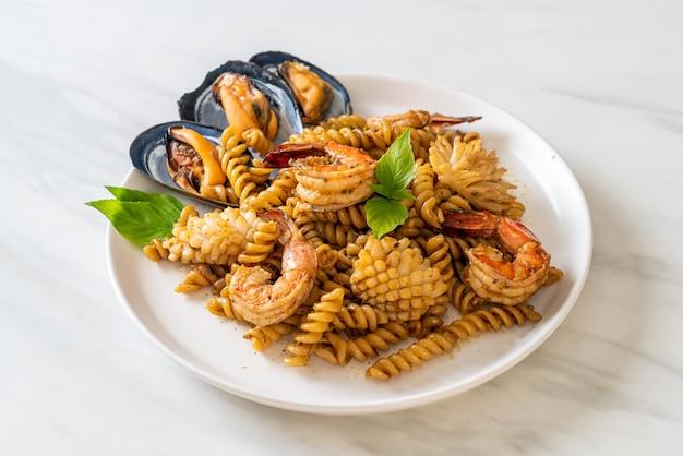 Roergebakken spiraalpasta met zeevruchten en basilicumsaus. fusion food-stijl