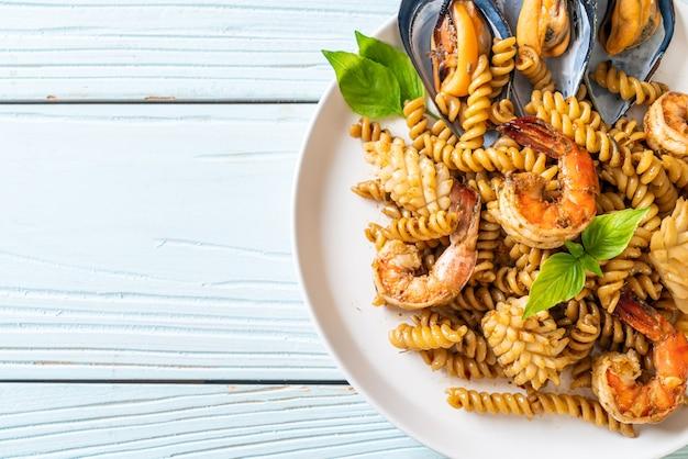 Roergebakken spiraalvormige pasta met zeevruchten en basilicumsaus - fusion food-stijl