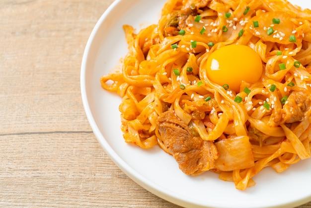 Roergebakken udon noedels met kimchi en varkensvlees - koreaans eten food