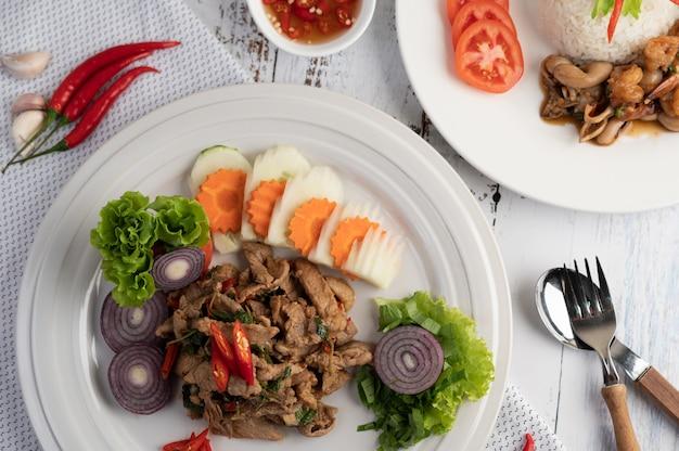 Roergebakken varkensvlees basilicum op een witte plaat met wortelen, komkommer en ui.