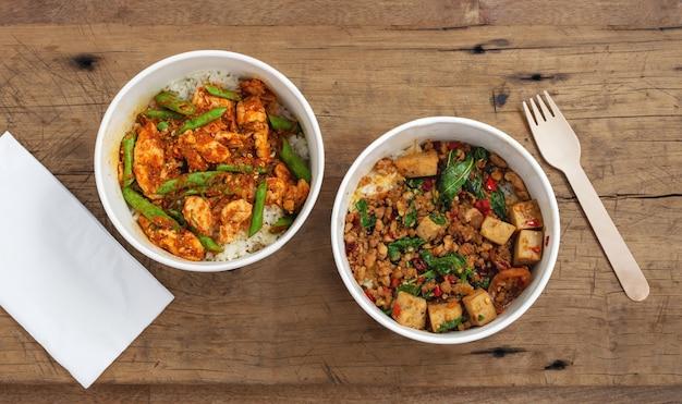 Roergebakken varkensvlees en kip met rijst in dozen van voedselpapier