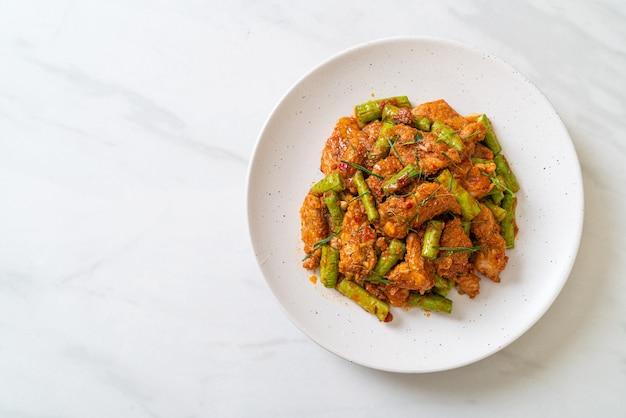 Roergebakken varkensvlees en rode currypasta met stekboon, aziatische eetstijl