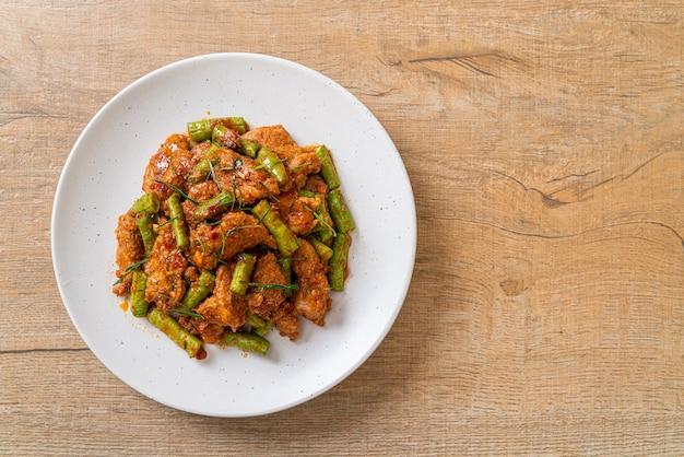 Roergebakken varkensvlees en rode currypasta met stekboon - aziatische eetstijl