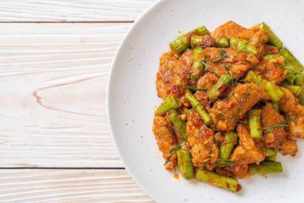 Roergebakken varkensvlees en rode currypasta met stekboon. aziatische eetstijl