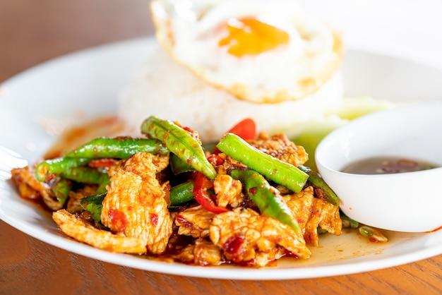 Roergebakken varkensvlees in rode currypasta met rijst en gebakken ei