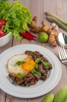 Roergebakken varkensvlees met basilicum, gebakken ei in een witte schotel.