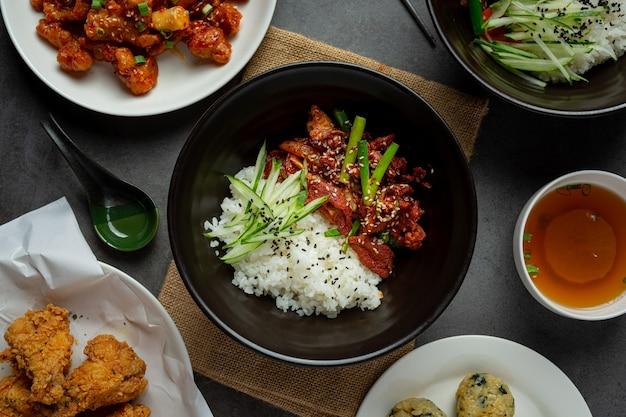 Roergebakken varkensvlees met koreaanse saus op donkere achtergrond