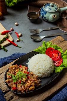 Roergebakken varkensvlees, zout en pepers, versierd met thaise ingrediënten.