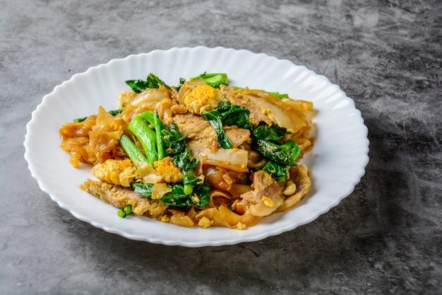 Roergebakken verse rijstmeel noedels met gesneden varkensvlees, eieren en boerenkool. snelle noodle-roerbakken.
