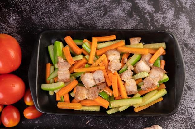 Roergebakken wortelen en komkommer met buikspek.