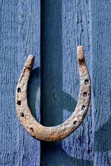 Roestig ijzeren hoefijzer genageld aan houten muur