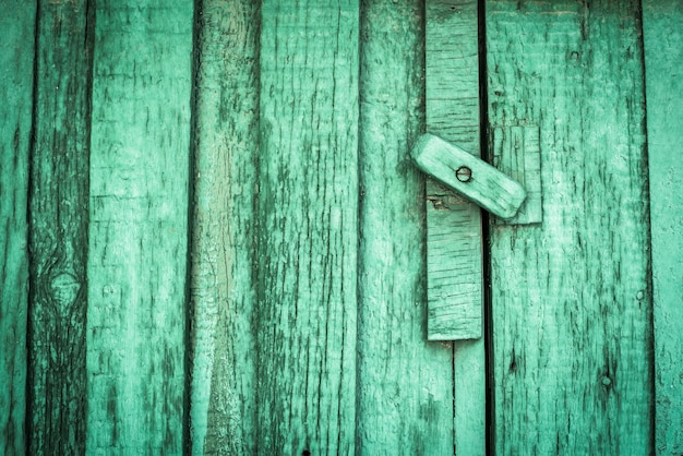Roestig slot op een textuur van oud, houten, groen tij, celadondeur, die de oude verf afbladdert. de doorgang is afgesloten. op slot