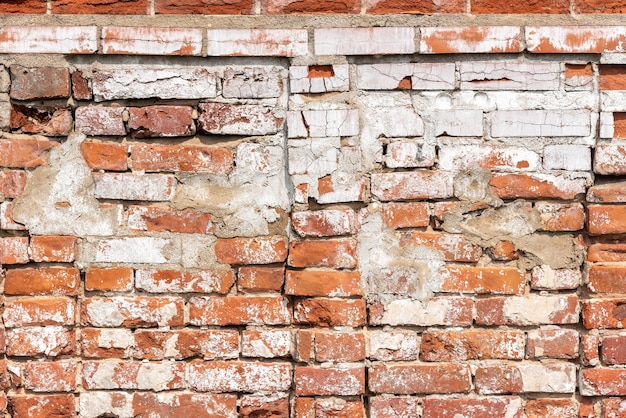 Roestige doorstane rode bakstenen muur met beton en gebroken delen. oude constructie of verweerd gebouw. loft of stedelijke stijl van interieur, achtergrond met kopie ruimte voor tekst. textuur of effect