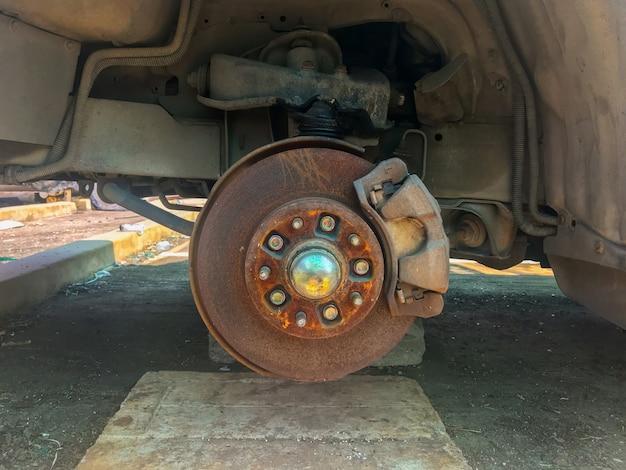 Roestige gebroken auto met ontbrekend wiel