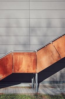 Roestige ijzeren trap met grijze muur