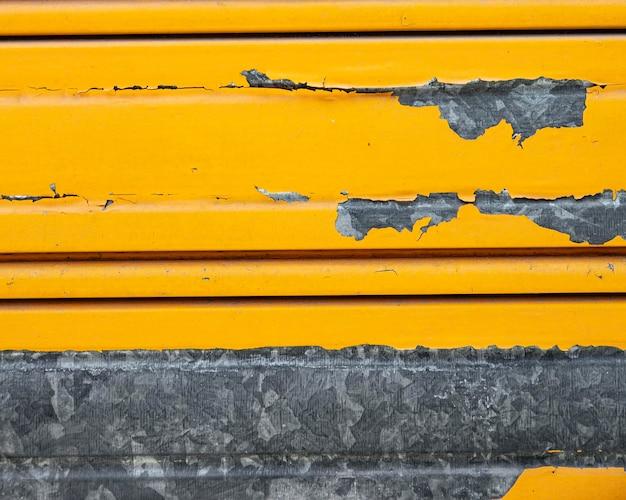 Roestige metalen wand met gele verf
