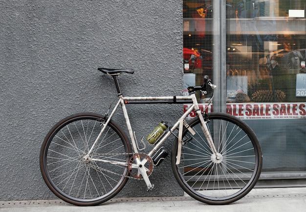 Roestige oude fiets dichtbij muur