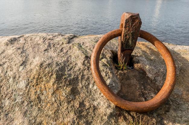 Roestige ring voor het aanmeren van een boot op de rots aan de oceaan