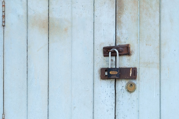 Roestige sleutels in het oude deurslot, gesloten oude uitstekende houten deur