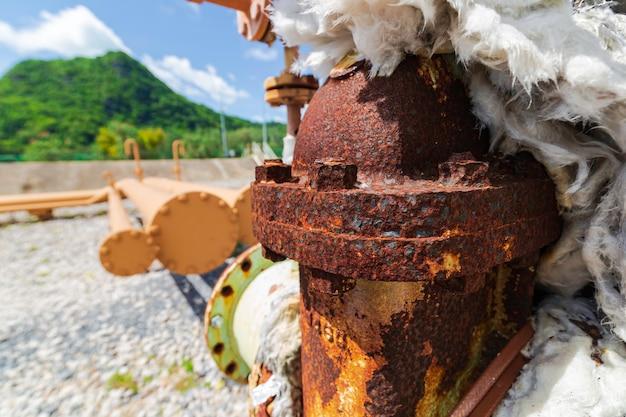 Roestschade aan verf en corrosieflens op de olie-ontluchtingstank van de pijpleiding van de klepisolatie.