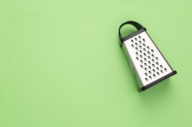 Roestvrijstalen rasp geïsoleerd keukenaccessoires hulpmiddelen om te koken geïsoleerd op groene achtergrond plat leggen
