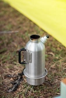 Roestvrijstalen waterkoker wordt op het fornuis geplaatst om water te koken voor koken en koffie. ochtend, kamperen