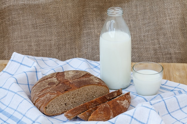 Rogge gesneden brood met fles melk op houten lijst