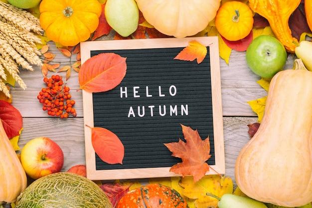 Rogge, pompoenen, appels, ashberry, meloen, kleurrijk gebladerte en letterbord met de woorden hallo herfst