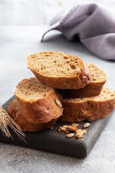 Rogge stokbrood gesneden op een grijze achtergrond met granen. volkorenbrood, een gezond voedingsconcept. kopieer ruimte.